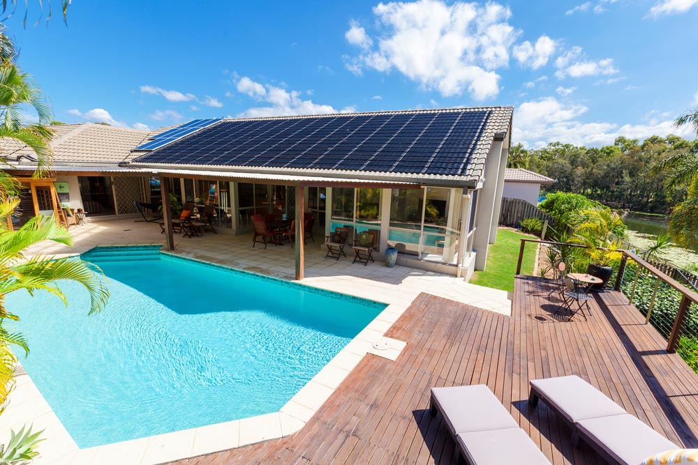 View Of A House With A Pool That Has Solar Panels On Roof Of House - Residential Solar Roofing Nashville - Music City Solar Solutions 2306 Eugenia Ave Suite A Nashville TN 37211 (615) 692-1602